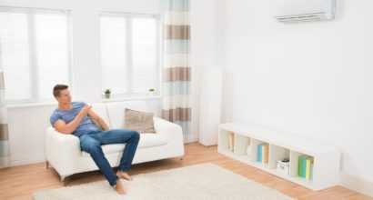 44592155 - young man on sofa operating air conditioner with remote control